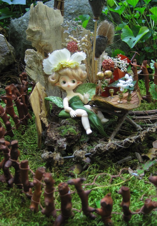 Brownie elf doll sitting on a bark bench with a tiny table