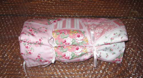 Sweet Pea wrapped in her cover tied closed with ribbon