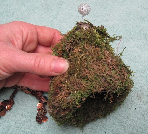 Christmas tree hat form partially covered in moss